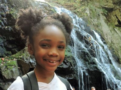 amachi kid with waterfall in background